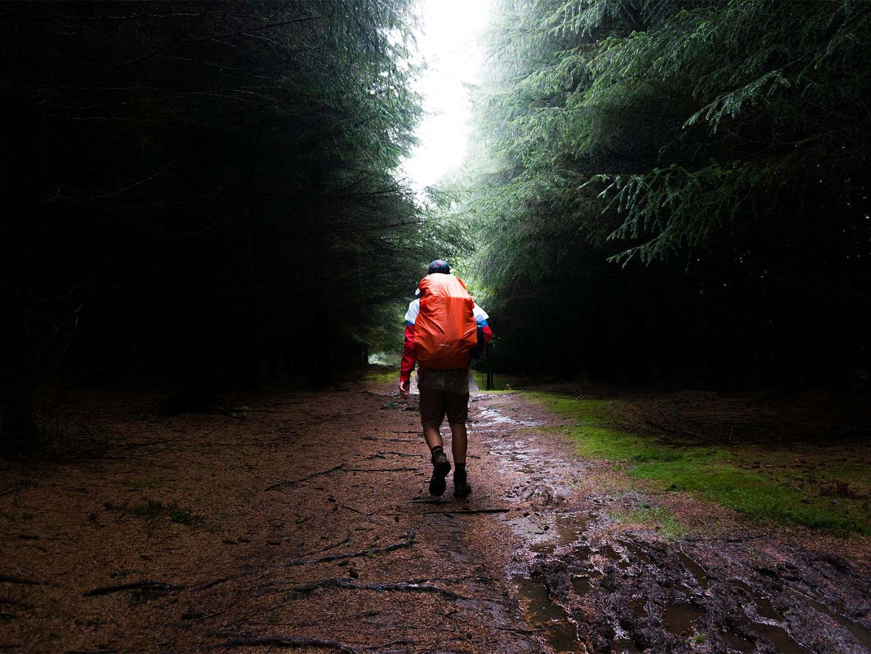 A lone hiker walks through a muddy trail, wearing the best men's waterproof boots.