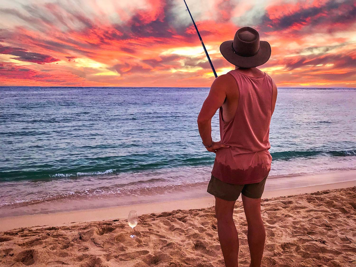 A man wearing the best fishing hat stands on the shores of the beach and fishes.