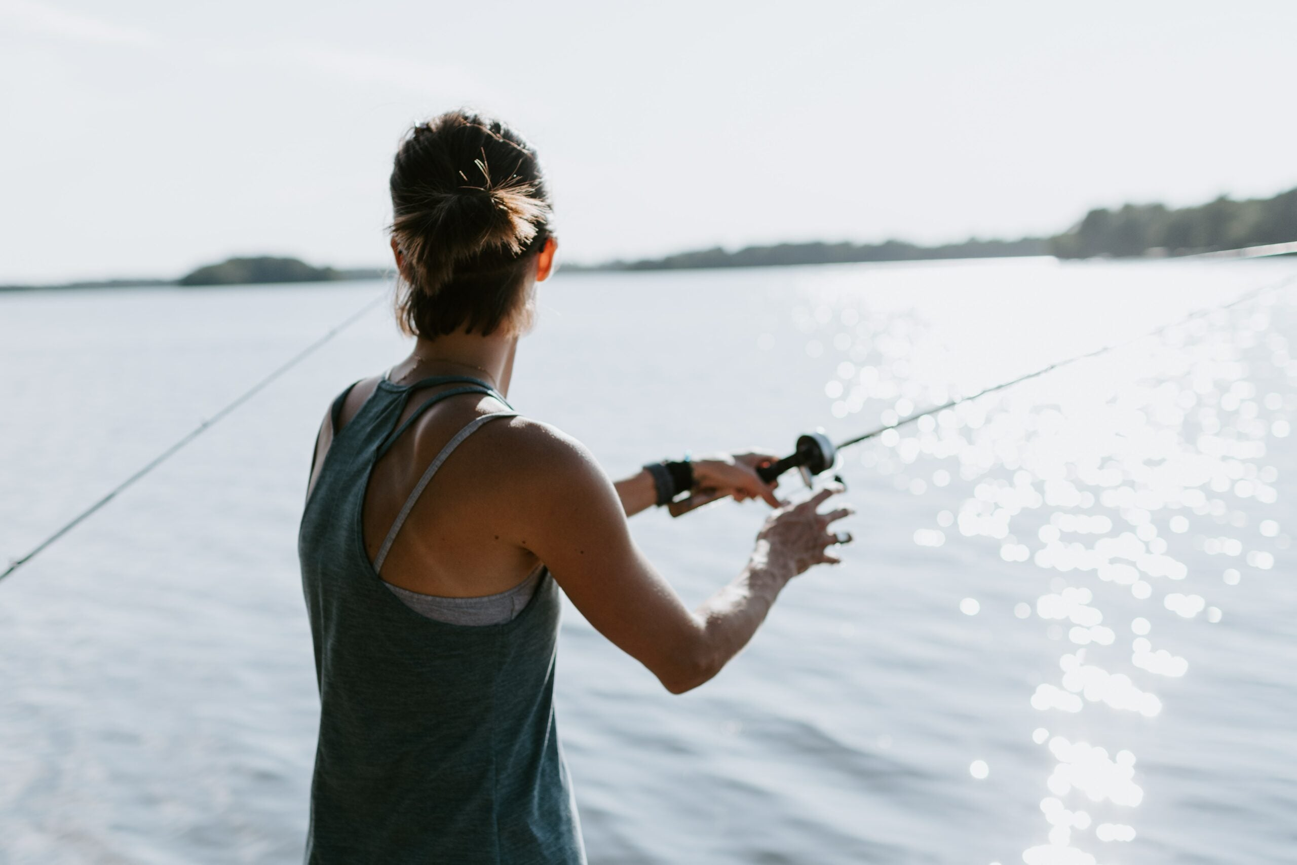 fishing gifts for moms. woman fishing on a lake.