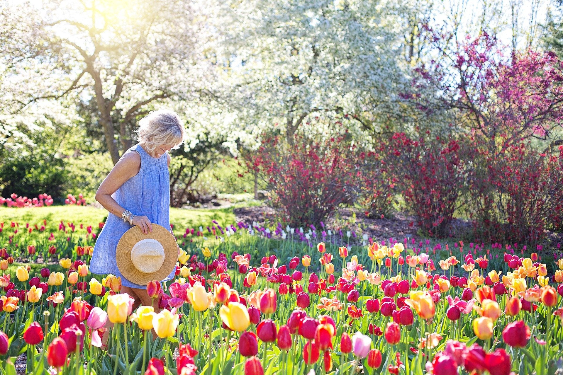 Best gifts for Mom. Woman walking through a field of flowers with a straw hat.