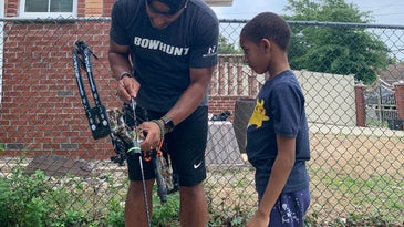 A bowhunter dad shows his son how to nock an arrow on the string of a compound bow.