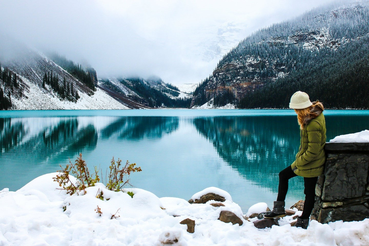 A hiker in a puffer jacket by a lake.