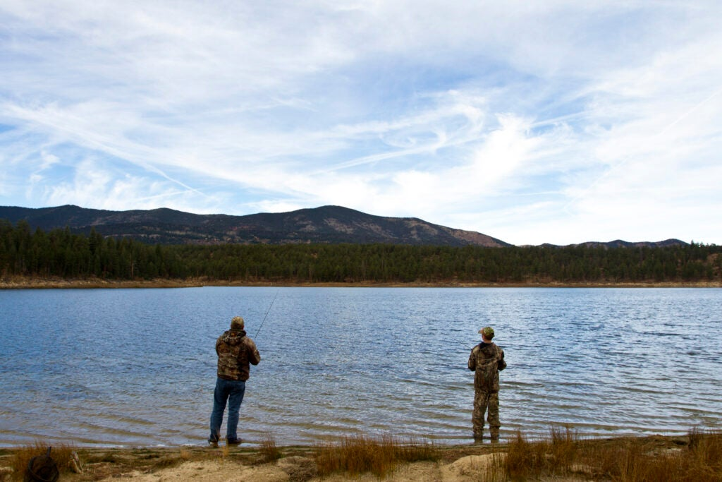 A father and son duo fish in a high-mountain like in New Mexico.