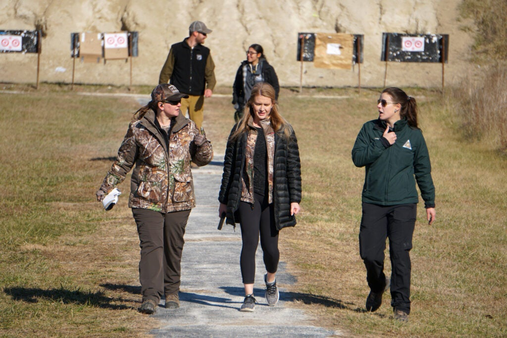 A group of women walking back from checking targets at the shooting range.