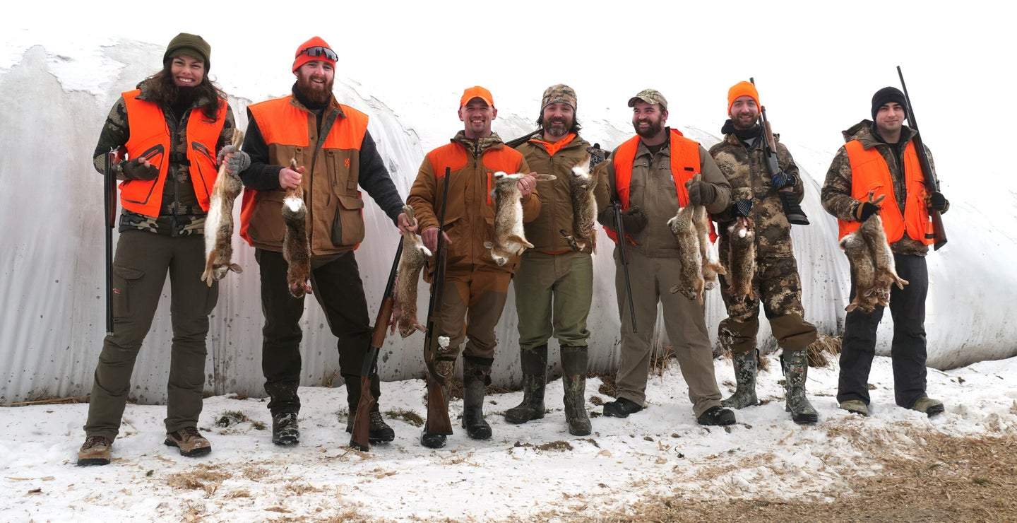 A group of happy rabbit hunters in blaze orange and camo on a snowy day.