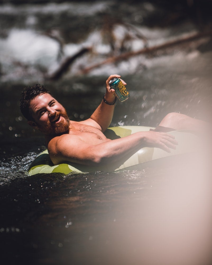 A man in a float tube smiling and drinking a can of beer.