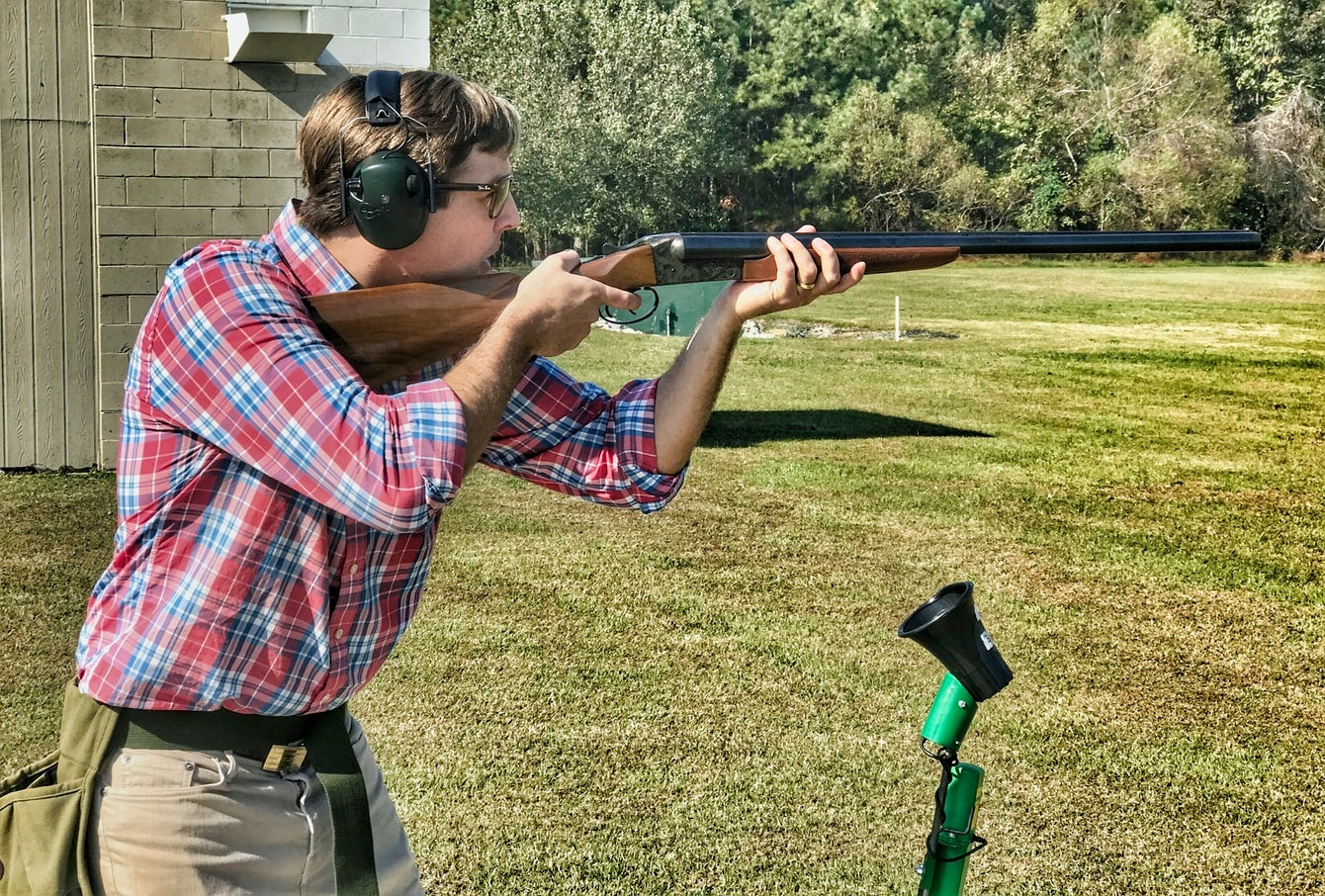 A shooter wearing ear protection at a clays range readies to shoot.