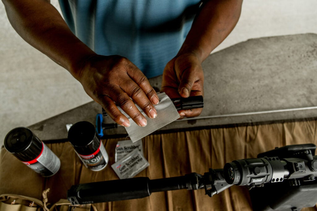 A man at the shooting range cleans the bolt of his firearm.