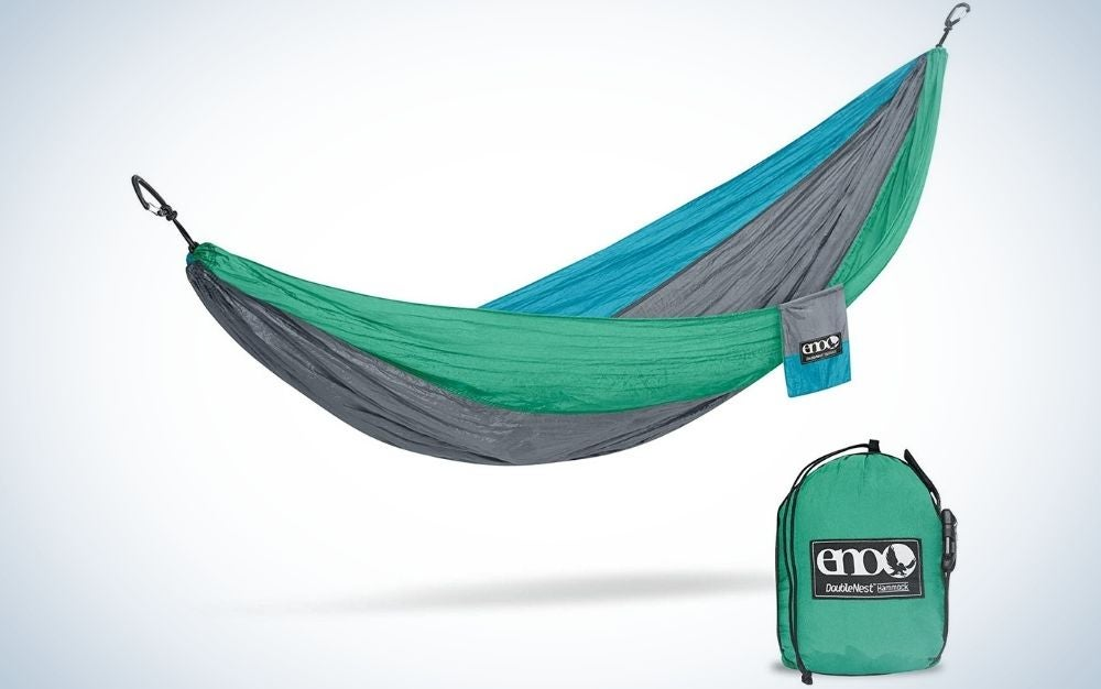 A green, blue and grey outdoor hammocks and near to it a green storage bag.