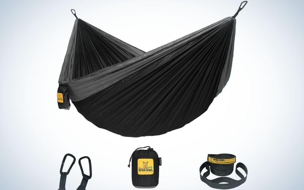 A black hammock camping double with tree straps and two packing bags.