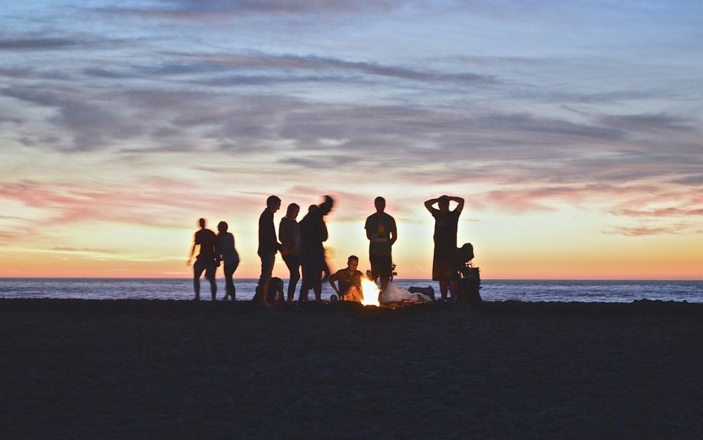 A group of people around the fire during sunset into the beach.