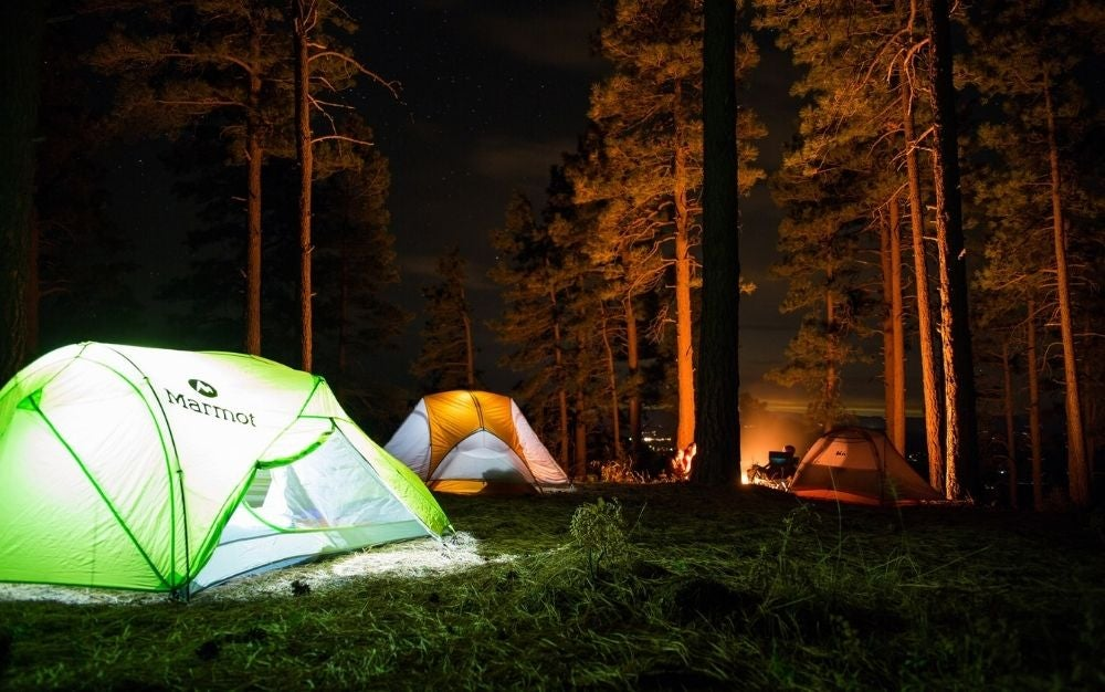 Two lighten tents, green and orange tents into the forest in a dark night.