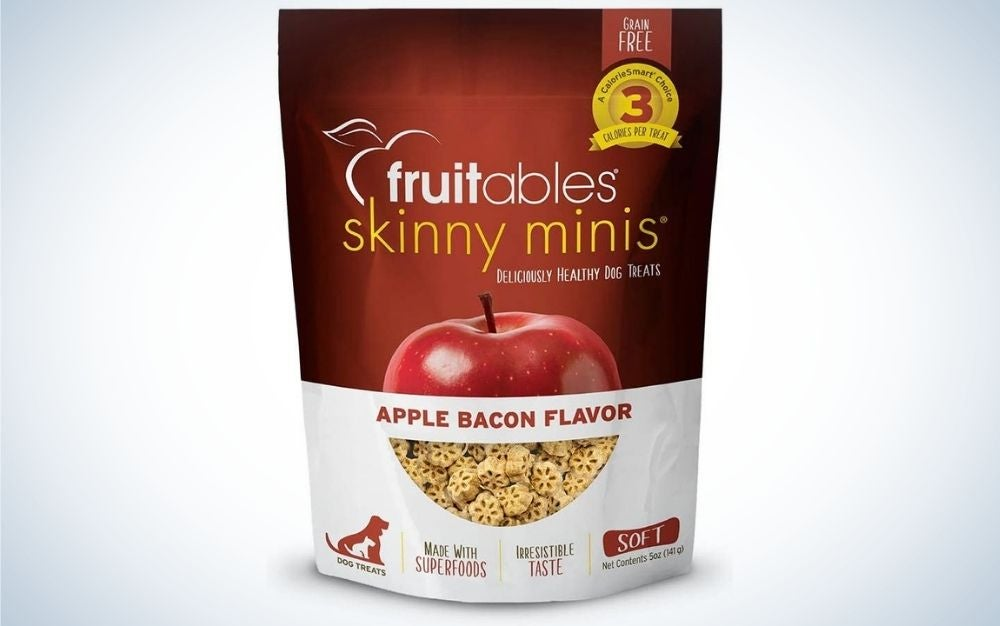 A cherry color nd white packing of a fruitables skinny minis' dog treat with a half apple and bacon flavor under it.