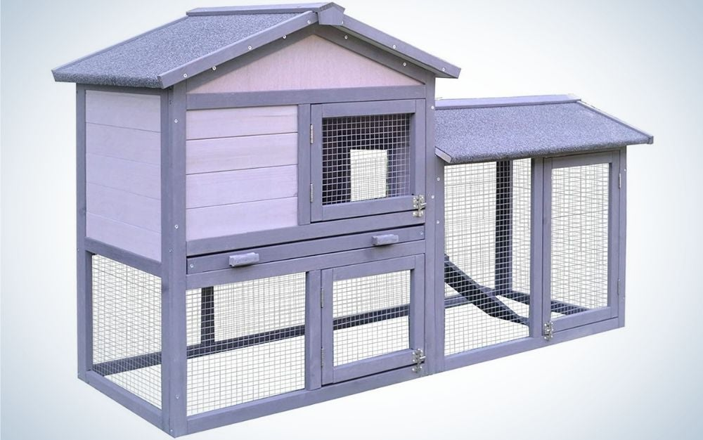 A large rabbit hutch with grey wood with a large open run area, an internal ramp and four lockable doors on the front of the hutch.