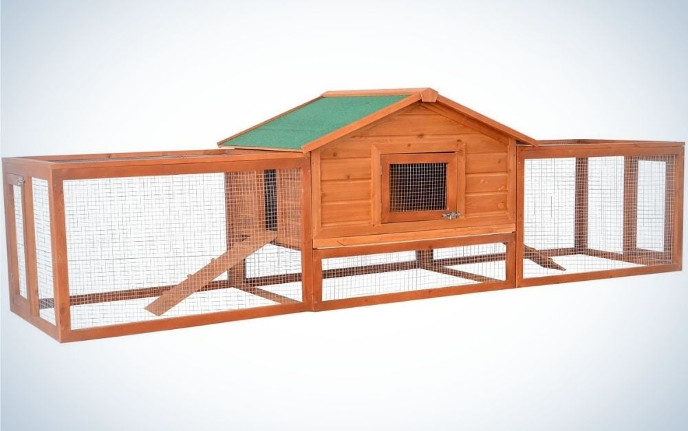 A large wooden rabbit hutch pet house with ramps, lockable doors, run area and green asphalt roof for outdoor use.