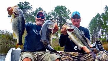 Two bass anglers with big florida-strain fish.