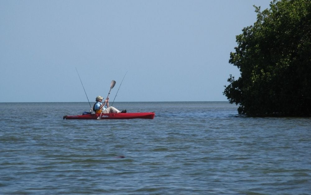 A man with hat on kayak sailing on the blue sea.
