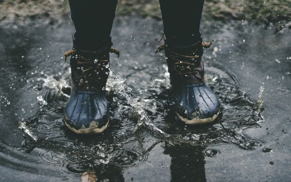 Woman wearing blur rubber sole boots with laces for fastening standing on splashed water.