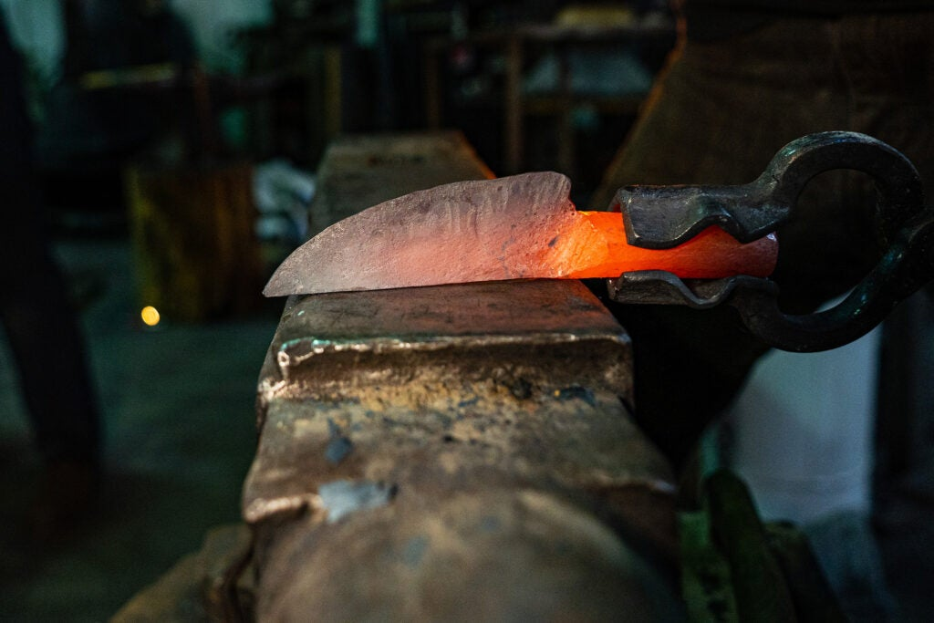 A piece of steel being shaped into a knife.