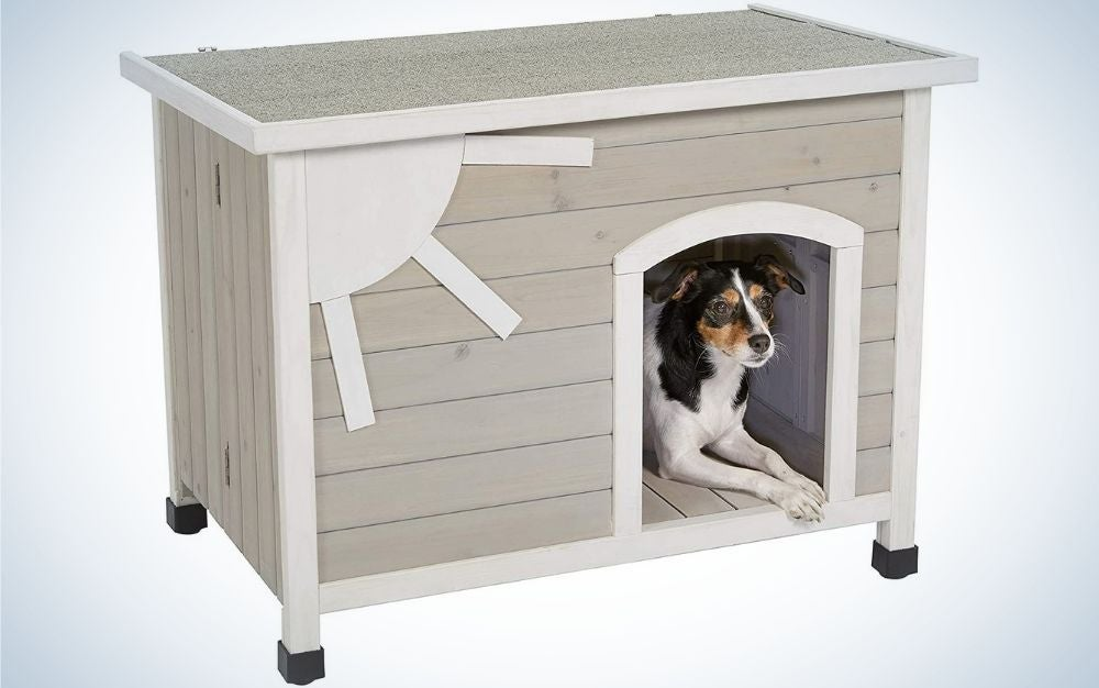 A gray wooden house for the dog with four layers and a small dog standing at its entrance.