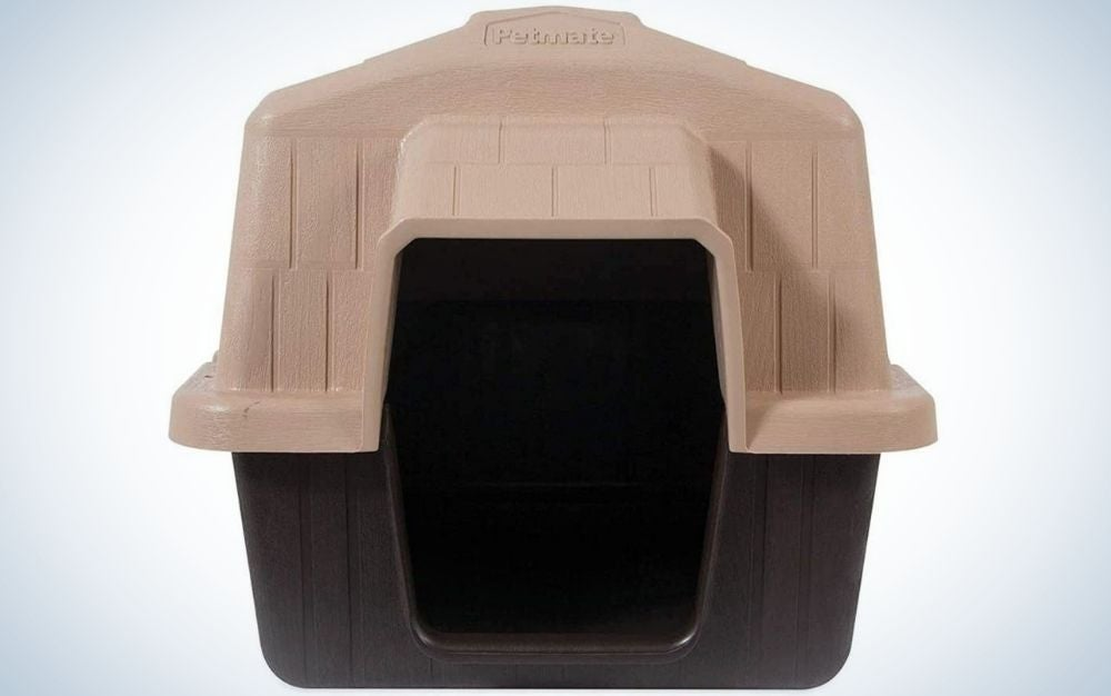 A small dog house covered with a pink roof and black bottom.