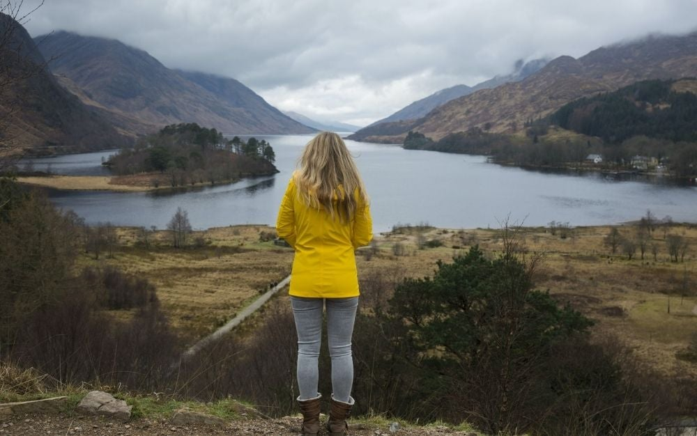 A blonde woman with yellow jacket standing staring the big lake between mountains.