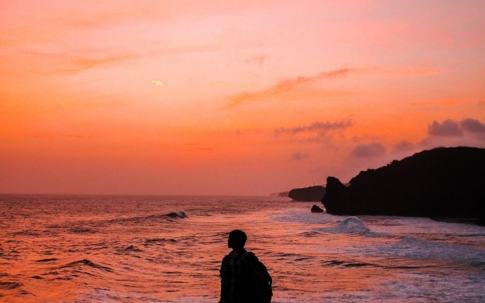 A man standing by the sea and watching the sunset.