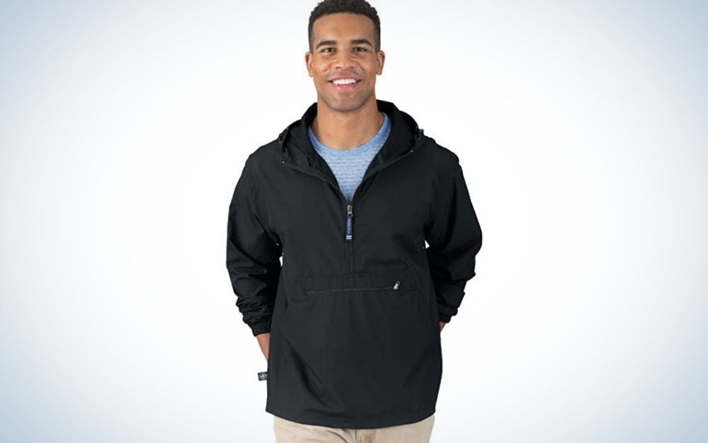 A man smiling and posing with a lightweight black rainy