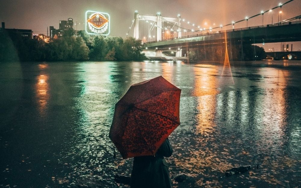 A person under a red umbrella standing and looking the sea and a big bridge in lights.