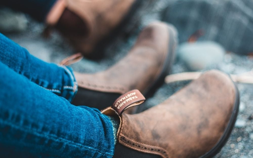 Foots of a man with jeans and with brown boots resting.
