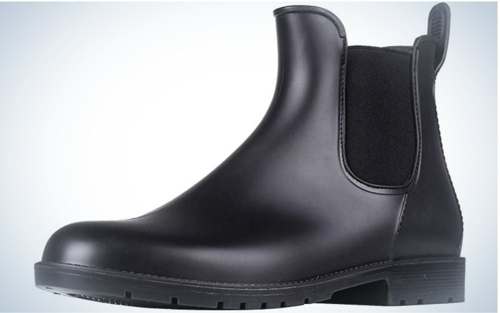 A black boot made entirely of leather material and with the elastic part on the side and a strong sole.