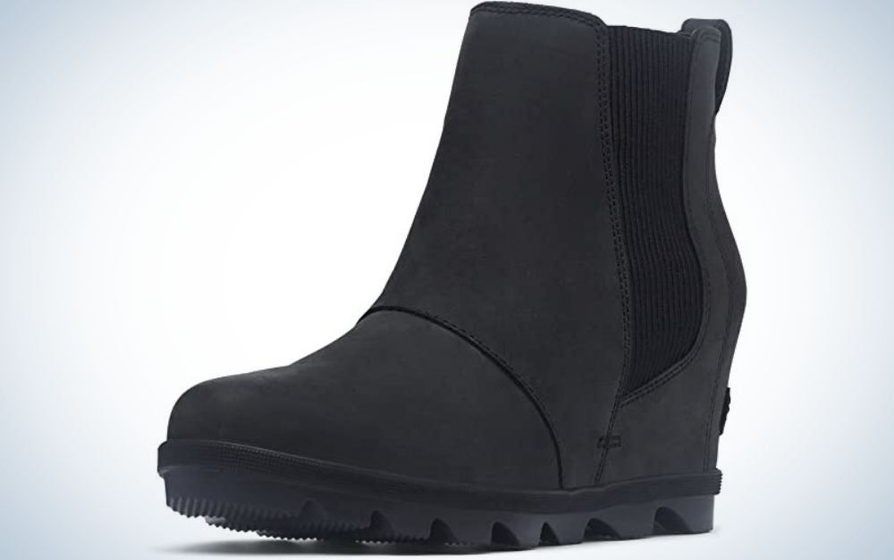 A black boot made entirely of suede material and with the elastic part on its side and a strong sole a little high.