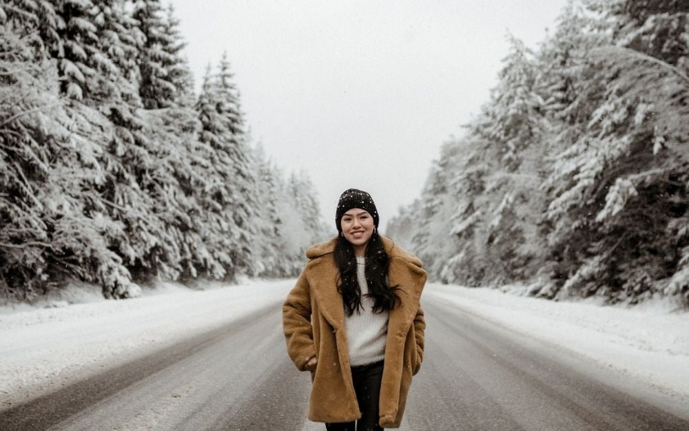 A girl smiling and walking into a snowy road between some trees, while wearing a long and comfortable warm brown jacket.