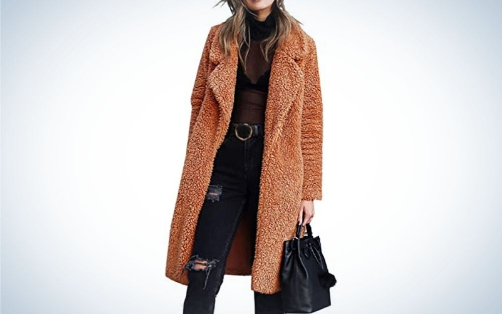 A girl posing while wearing a long warm jacket in brown and orange color.