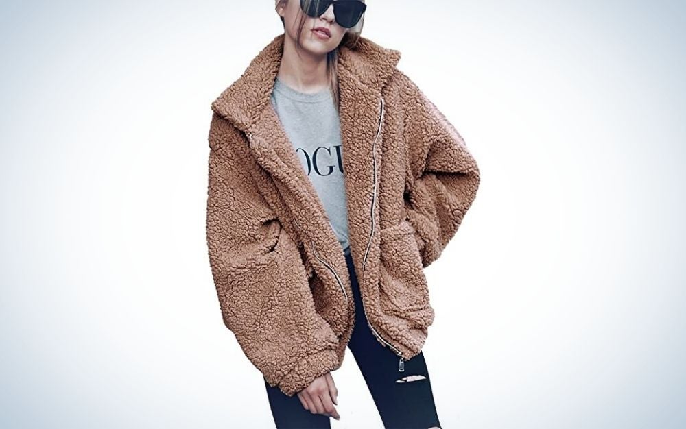 A girl posing while wearing a big warm brown jacket with a shirt and black jeans.
