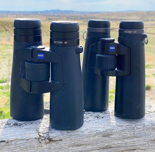 Two pairs of black Zeiss Victory RF binoculars standing straight up