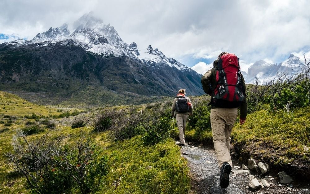 Two people with camping backpacks walking through a green field among the mountains.