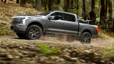 The Ford F150 lightning driving down a trail.