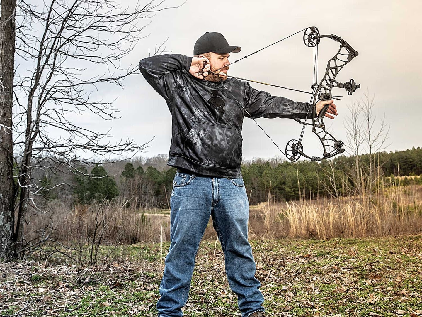 Guy at full draw with a compound bow