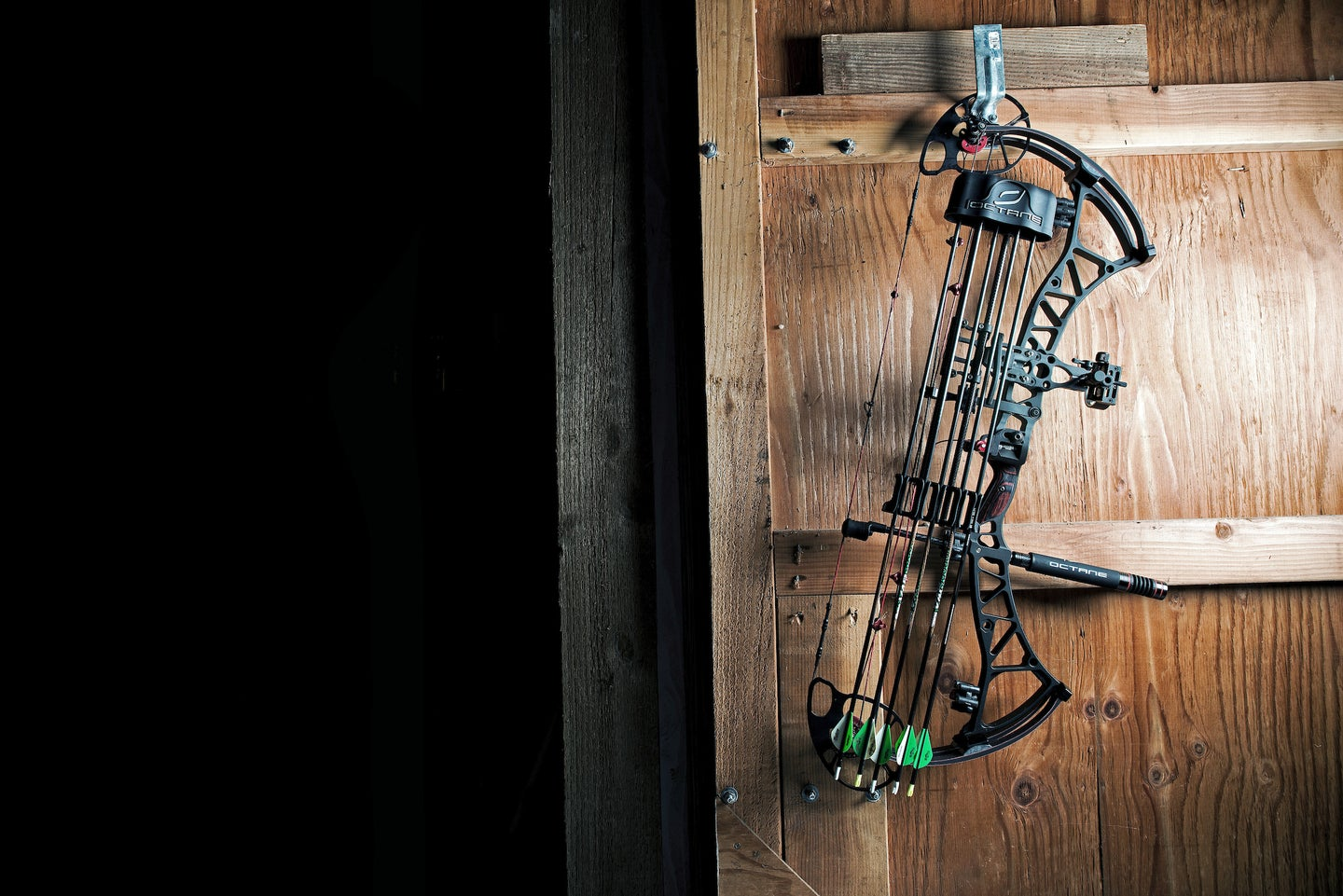 Compound bow hanging on barn door