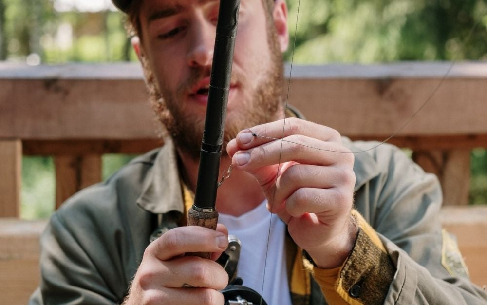 A bearded man wearing a green jacket who is arranging a black spinning rod.