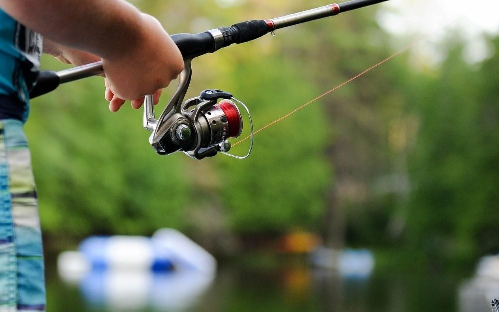 An angler turns a spinning reel.