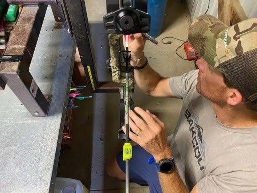 Man tuning his PSE stinger max hunting bow