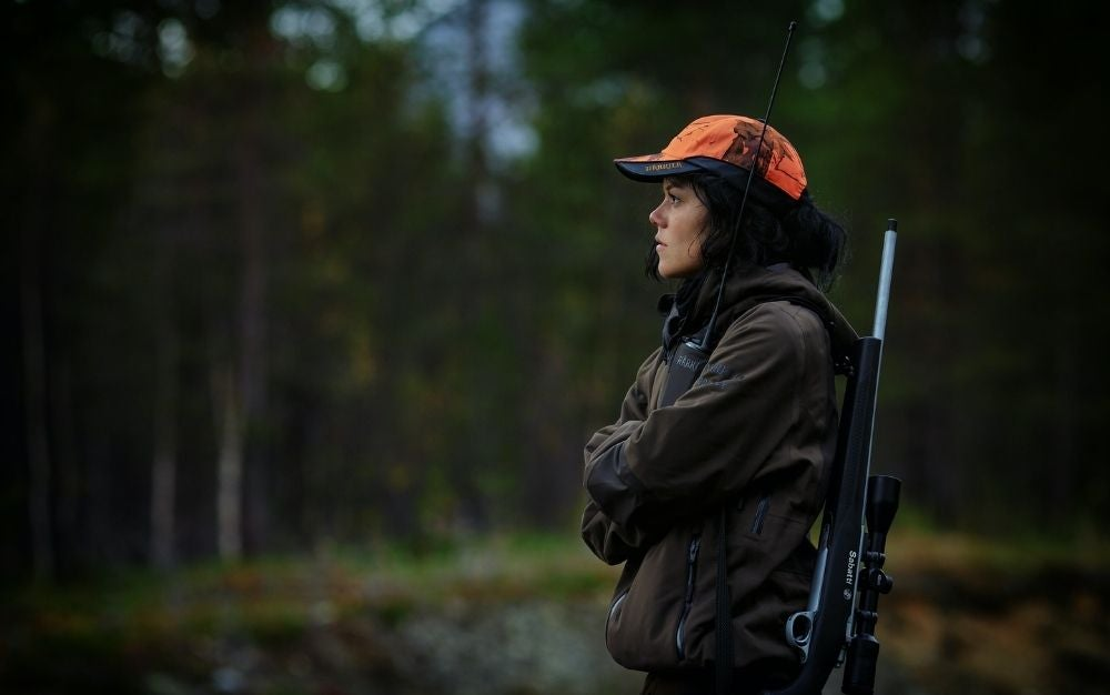 Woman hunting with a rifle slung over her shoulder
