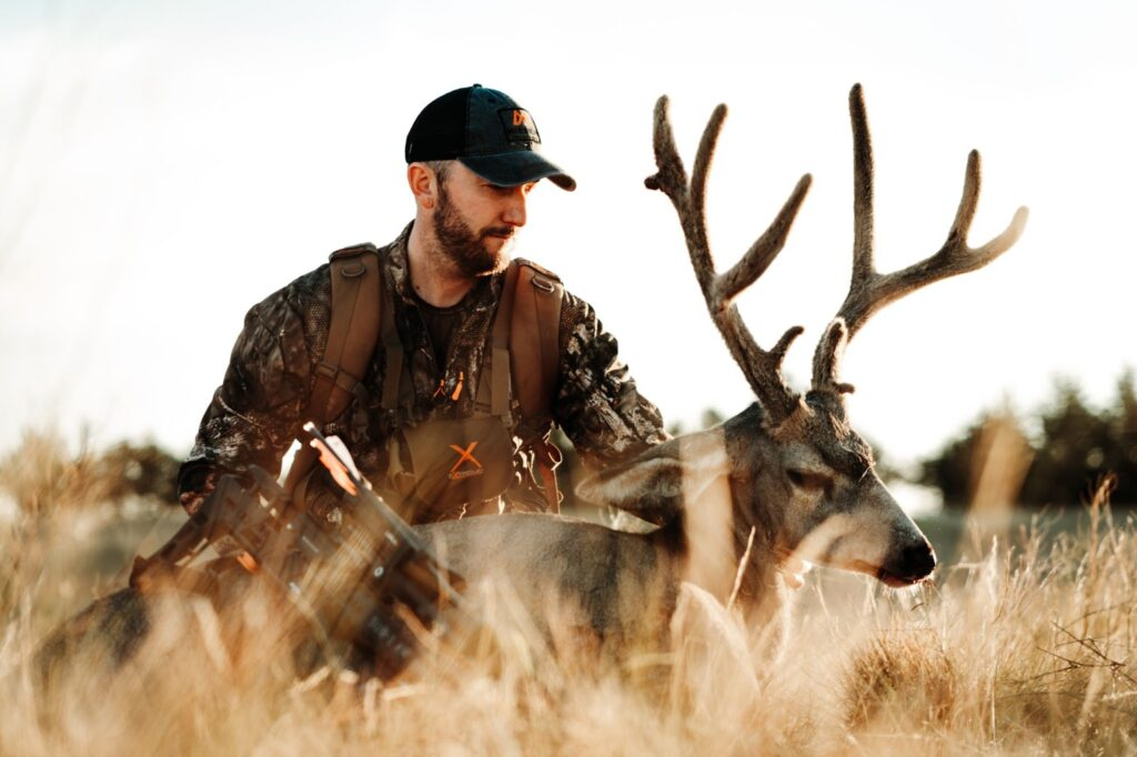 Hunter holding up mule deer shot with Mission Sub-1 crossbow
