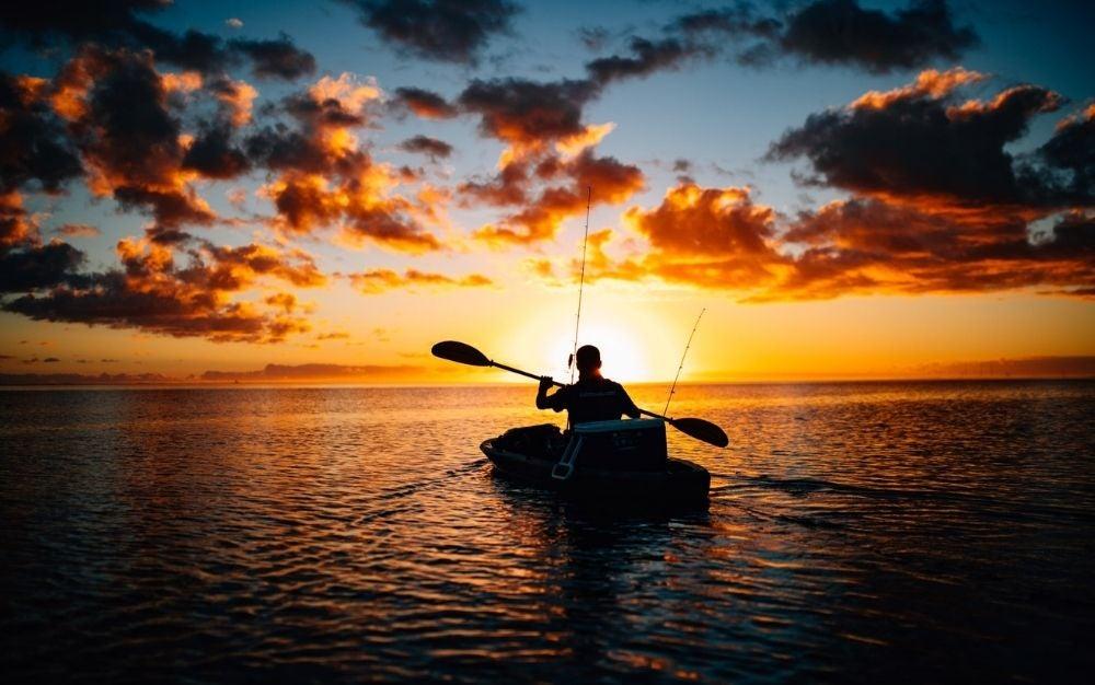 A fisherman paddling a kayak.