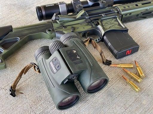 Vortex fury binoculars next to a gun and ammo.