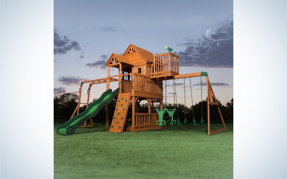 A playground with wooden spaces and mini rooms, with some small steps to climb next to it and four slides and a green slide.