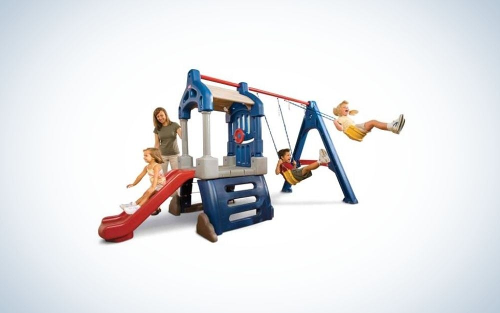 A mother and three children playing in a playground outside, with a metal structure and a red slide, and two yellow sliders.