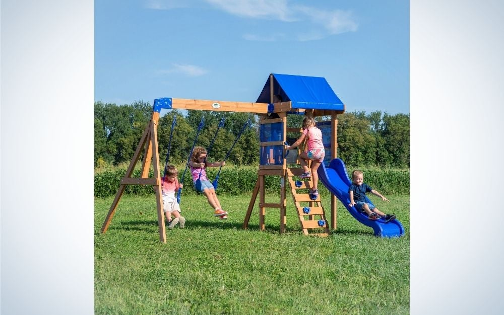 Four children playing in an outdoor playground on a grassy field, two children do the laundry, one climbs the stairs and the other is on the sidewalk.